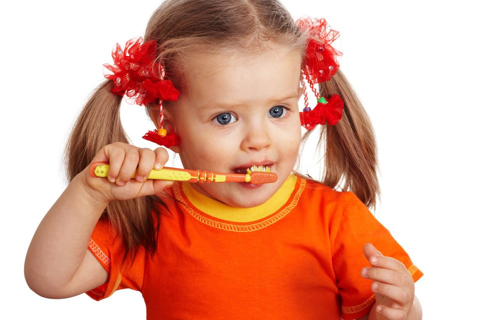 photo of a child brushing her teeth