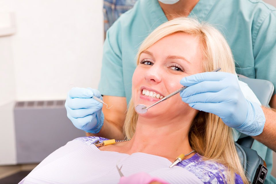 photo of a woman doing oral checkup at the local dentist office