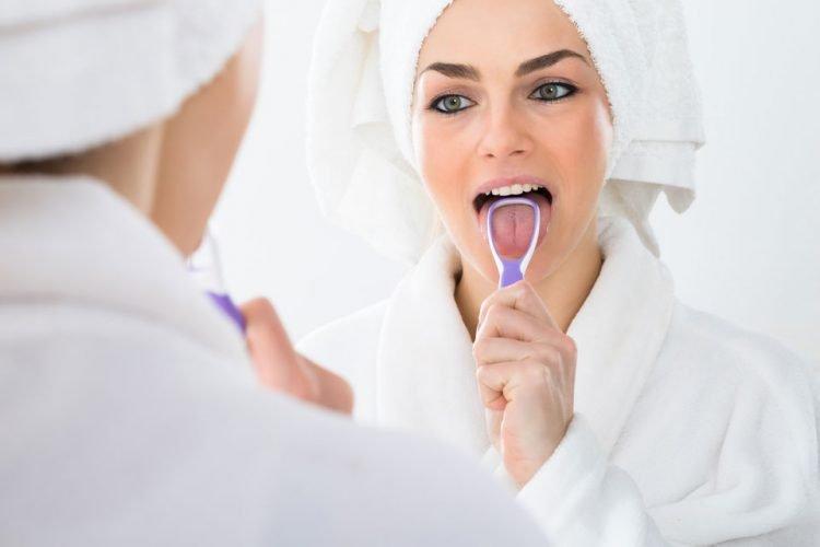 a photo of a woman using tongue scraper